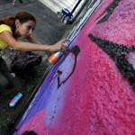 A woman paints a graffiti during a demos