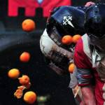 Men wearing helmets are hit by oranges d