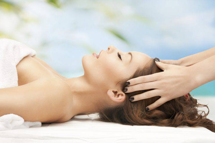 people, health care and relax concept - close up of woman on resort getting head spa treatment