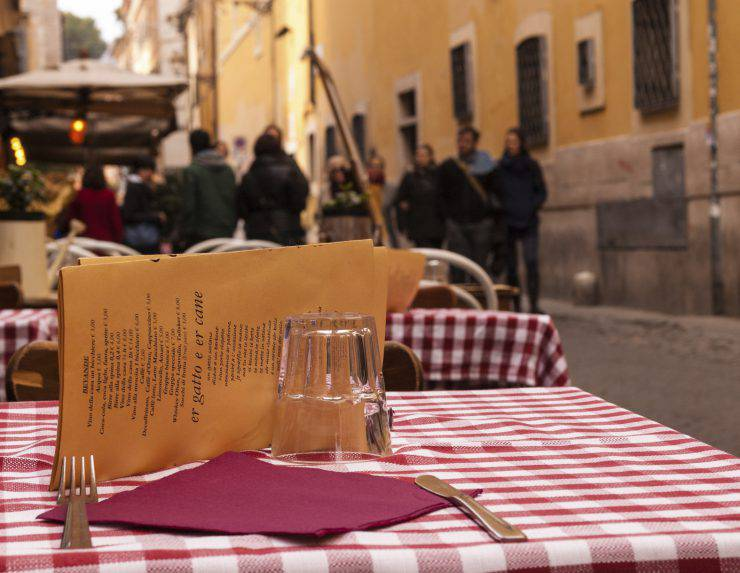 Close-up on a table of an outdoor Italian restaurant with medieval alley and people walking in the background