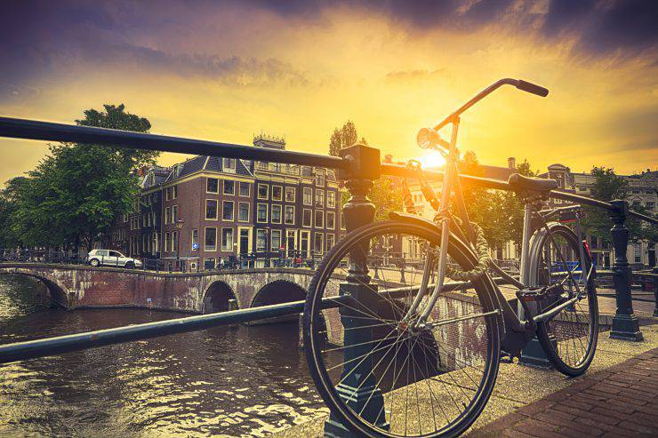 Sun beam coming through bicycle by water canal in Amsterdam.