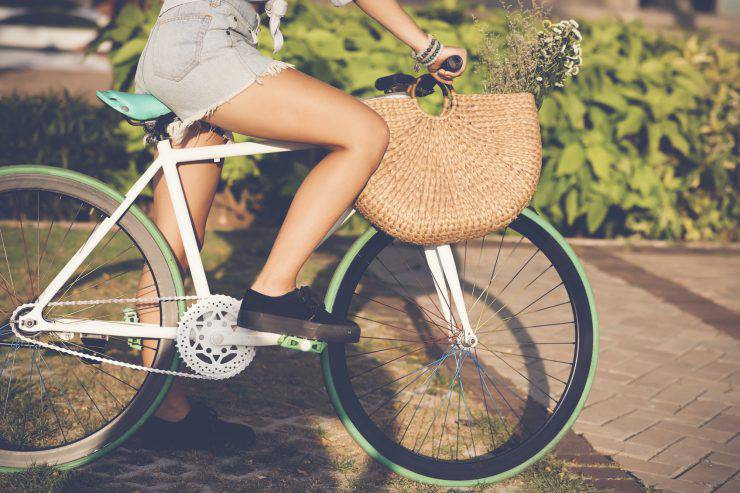 Cropped image of girl in denim shorts riding bicycle