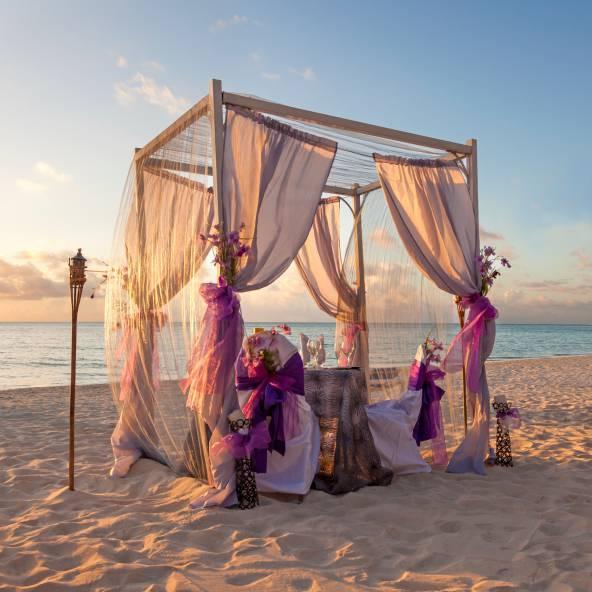 In un gazebo romantico sulla spiaggia ad ammirare il tramonto.