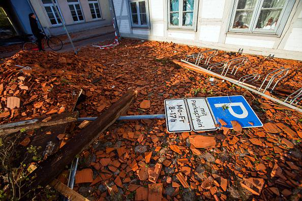 A parking sign lays amidst tiles blown away from roofs by a tornado on a street in Buetzow, northeastern Germany, on May 6, 2015. One man was killed and more than 30 people injured when a tornado and violent storms hit northern Germany, ripping tiles off roofs, downing trees and overturning cars, emergency services said.      AFP PHOTO / DPA / JENS BUETTNER   +++   GERMANY OUT        (Photo credit should read JENS BUETTNER/AFP/Getty Images)
