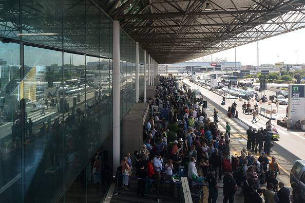 "Travellers wait outside Rome's Fiumicino international airport where a fire broke out overnight at Terminal 3, on May 7, 2015. Several airport employees were treated for smoke inhalation but there were no serious injuries as a result of a blaze which took hold overnight in terminal three of the Italian capital's main airport. The Rome airports authority ADR said the cause was ""probably a short circuit."" Police do not suspect any foul play. AFP PHOTO / TIZIANA FABI        (Photo credit should read TIZIANA FABI/AFP/Getty Images)"