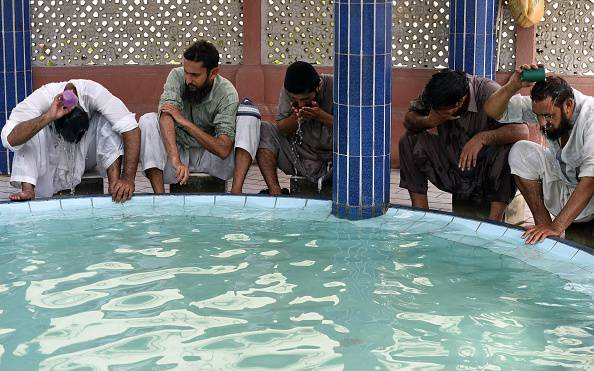 Pakistani Muslims cool themselves with water at a mosque during a heatwave in Karachi on June 22, 2015. Nearly 200 people have died in a heatwave in southern Pakistan, officials said as the government called in the army to help tackle widespread heatstroke in the worst-hit city Karachi. AFP PHOTO / ASIF HASSAN        (Photo credit should read ASIF HASSAN/AFP/Getty Images)