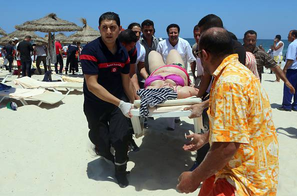 Tunisian medics carry a woman on a stretcher in the resort town of Sousse, a popular tourist destination 140 kilometres (90 miles) south of the Tunisian capital, on June 26, 2015, following a shooting attack. At least 38 people, including foreigners, were killed in a mass shooting at a Tunisian beach resort packed with holidaymakers, in the North African country's worst attack in recent history. AFP PHOTO / MOHAMED FLISS (Photo credit should read MOHAMED FLISS/AFP/Getty Images)