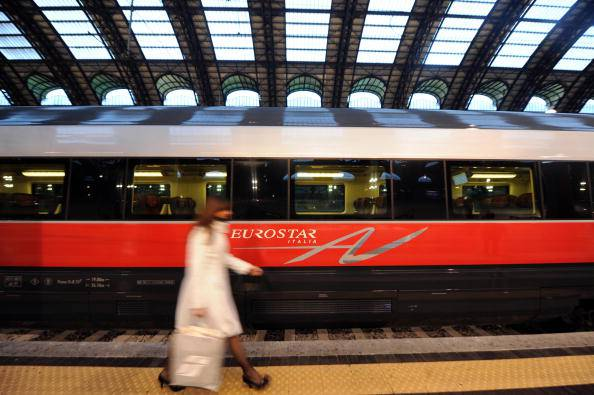 "A train hostess walks in front of a ""Freccia Rossa"" (Red Arrow) high speed train on the day of its launching on December 13, 2008 at Milan Central station. The Freccia Rossa high speed train of Italian company Trenitalia will reduce the travel time from Milan to Rome to three-hour and a half from December14 and to three-hour at the end of 2009.   AFP PHOTO / GIUSEPPE CACACE (Photo credit should read GIUSEPPE CACACE/AFP/Getty Images)"