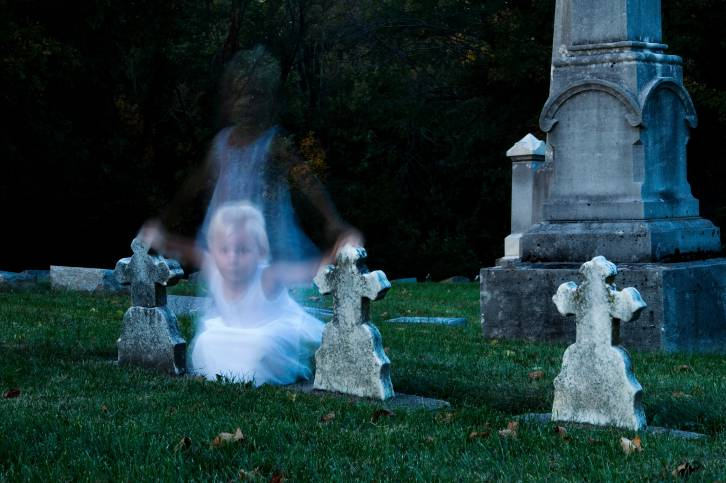 Ghost of young girl hovers between cross-topped gravestones