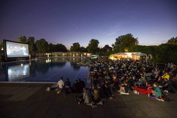 LONDON, ENGLAND - JULY 17:  Members of the public watch an outdoor screening of the film 'Jaws' in Brockwell Lido at night on July 17, 2014 in London, England. The outdoor screening was arranged by 'The Luna Cinema' who show classic films on big screens in interesting settings such as: parks, manor houses, castles, swimming pools, theatres and ruined abbeys.  (Photo by Oli Scarff/Getty Images)