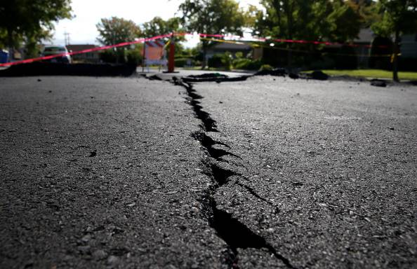 NAPA, CA - AUGUST 26:  A crack runs down the center of an earthquake-damaged street on August 26, 2014 in Napa, California.  Two days after a 6.0 earthquake rocked the Napa Valley, residents and wineries are continuing clean up operations.  (Photo by Justin Sullivan/Getty Images)
