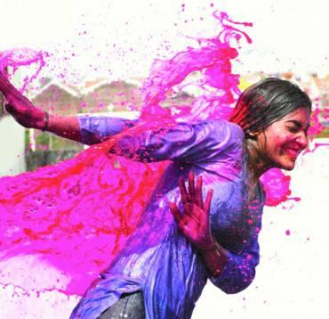 Splash of wet colors on female during Holi celebration.