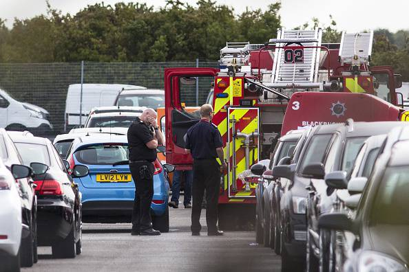 Members of the emergency services attend the scene of a plane crash at a car park next to Blackbushe Airport, in Hampshire on August 1, 2015. Members of Osama Bin Laden's family were among the victims in the crash of a private jet in Britain, the Saudi embassy in London said Saturday in a message of condolences. Four people died when the Saudi Arabia-registered plane ploughed into a car auction site and burst into flames in southern England on Friday. AFP PHOTO / JACK TAYLOR        (Photo credit should read JACK TAYLOR/AFP/Getty Images)