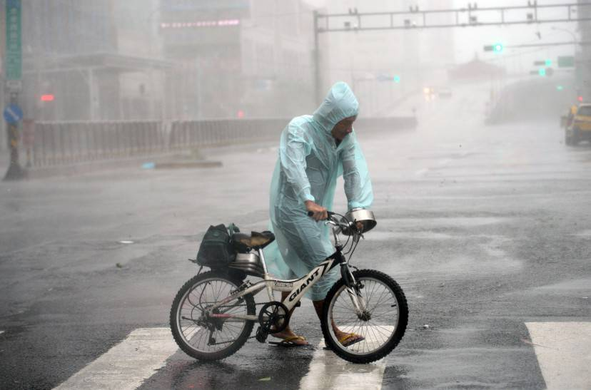 A man holds his bike as typhoon Soudelor hits Taipei on August 8, 2015.  Typhoon Soudelor battered Taiwan with fierce winds and rain leaving four people dead and a trail of debris in its wake as it takes aim at mainland China.  AFP PHOTO / Sam Yeh        (Photo credit should read SAM YEH/AFP/Getty Images)