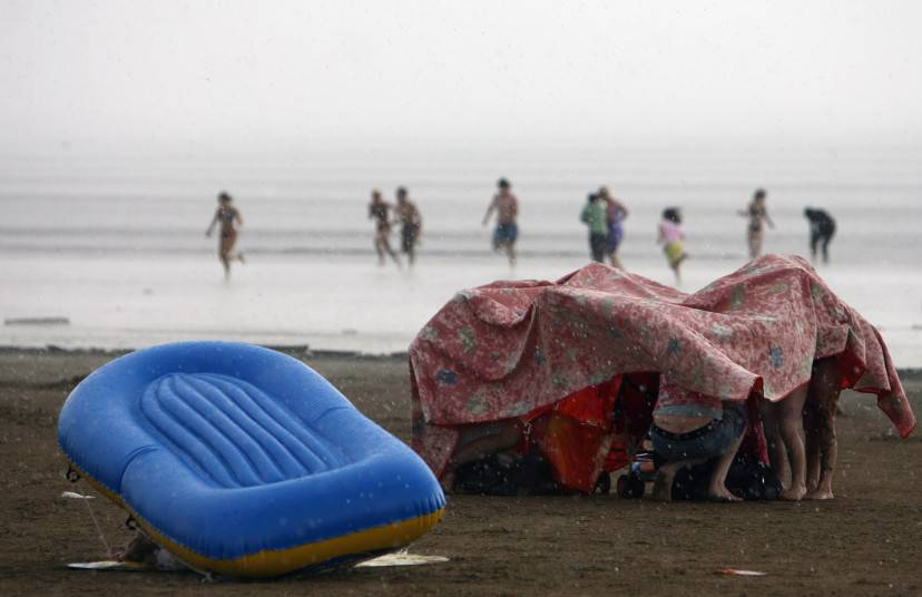 WESTON-SUPER-MARE, UNITED KINGDOM - JULY 28:   Holiday makers are caught in a sudden rain storm on the beach close to the Grand Pier on July 28 2008 in Weston-Super-Mare, England. A major fire has destroyed most of the Grade II-listed Grand Pier in the Somerset seaside resort  (Photo by Matt Cardy/Getty Images)