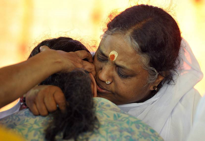 Indian spiritual figure Mata Amritanandamayi (R), known by her followers as amma (mother), hugs a devotee during an event in Hyderabad on March 15, 2015. Mata Amritanandamayi, popularly known as the 'hugging saint', is on a two-day visit in the southern Indian state of Telangana as part of her 'Bharat Yatra' tour. AFP PHOTO/ Noah SEELAM        (Photo credit should read NOAH SEELAM/AFP/Getty Images)
