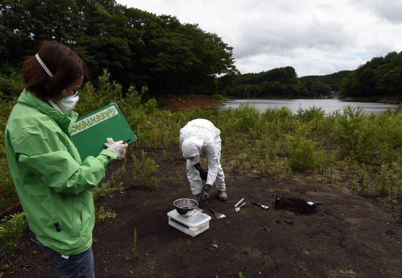 TO GO WITH Japan-nuclear-environment-energy,FOCUS by Natsuko Fukue  This photo taken on July 17, 2015 shows Greenpeace researcher Kazue Suzuki (L) logging information as colleague Jan Vande Putte (R) collects earth samples at the Ganbe Dam lakeside in the village of Iitate in Fukushima prefecture.  Iitate is significant because Japan's government did not order its evacuation until more than a month after the Fukushima nuclear accident began, but post-facto modelling of the radiation plume showed Iitate was right in its path.     AFP PHOTO / TOSHIFUMI KITAMURA        (Photo credit should read TOSHIFUMI KITAMURA/AFP/Getty Images)