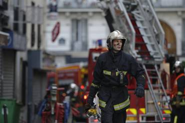 A firefighter works at the scene where a fire in an apartment building in the north of Paris killed eight people early on September 2, 2015. The fire in the eighteenth arrondissement, the cause of which is unknown, broke out at around 4:30 am (0230 GMT) and took more than 100 firefighters to contain it. The eight victims included two who died after they attempted to escape through windows, according to police. A source close to the investigation said two children were among the victims. AFP PHOTO / KENZO TRIBOUILLARD        (Photo credit should read KENZO TRIBOUILLARD/AFP/Getty Images)
