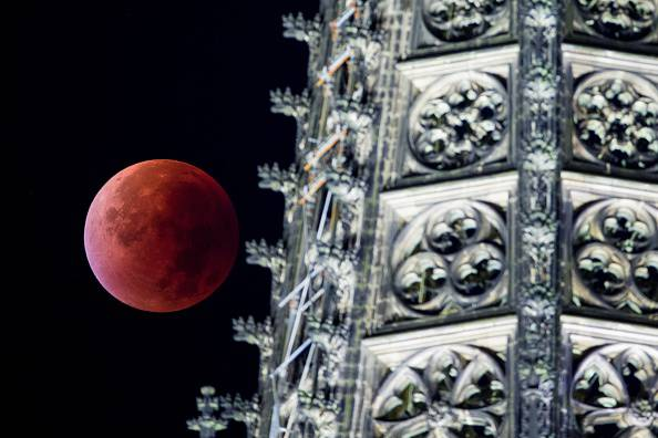 """A so-called """"blood moon"""" can be seen behind one of the steeples of the Cologne Cathedral during a total lunar eclipse in Cologne, western Germany, on September 28, 2015. Skygazers were treated to a rare astronomical event when a swollen """"supermoon"""" and lunar eclipse combined for the first time in decades, showing Earth's satellite bathed in blood-red light.    AFP PHOTO / DPA / ROLF VENNENBERND   +++   GERMANY OUT        (Photo credit should read ROLF VENNENBERND/AFP/Getty Images)"""