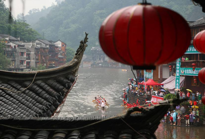 FENGHUANG COUNTY, CHINA - JUNE 8: (CHINA OUT) Competitors during a dragon boat race during the Duanwu Festival, or Dragon Boat Festival on June 8, 2008 in Fenghuang County of Hunan Province, China. The Duanwu Festival is celebrated throughout China every year with activities such as boat races and the eating of rice dumpings. The festival falls on the fifth day of the fifth lunar month and was established in remembrance of Qu Yuan, a patriotic poet who committed suicide in the Miluo River on the day in 221 BC. (Photo by China Photos/Getty Images)