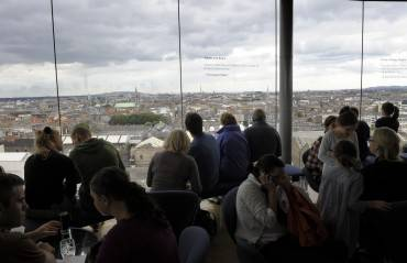 Visitors look at the city of Dublin from the top of the Guinness Storehouse, in Dublin on July 20, 2009. AFP PHOTO / MIGUEL RIOPA        (Photo credit should read MIGUEL RIOPA/AFP/Getty Images)
