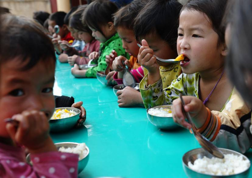 This picture taken on April 3, 2015 shows H'mong ethnic children eating a free lunch at a communal kindergarten at Meo Vac district, in the northern mountainous province of Ha Giang.  AFP PHOTO / HOANG DINH Nam        (Photo credit should read HOANG DINH NAM/AFP/Getty Images)