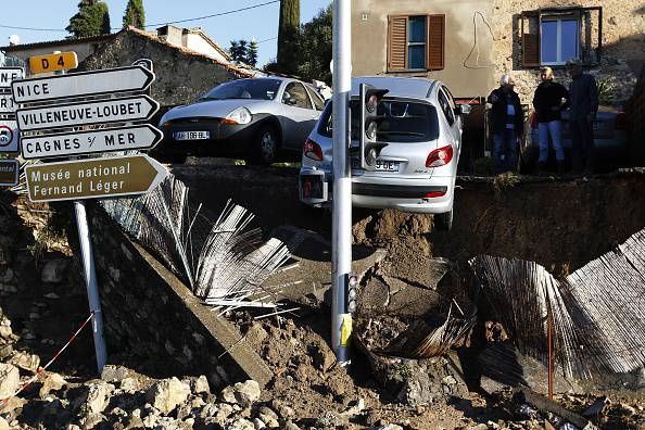 People look at the rubble in the aftermath of violent storms and floods in Biot, southeastern France, on October 4, 2015. Violent floods along the French riviera killed 13 people by early Sunday, emergency responders and local officials said, including three who drowned in a retirement home inundated when a river broke its banks.AFP PHOTO / JEAN CHRISTOPHE MAGNENET (Photo credit should read JEAN-CHRISTOPHE MAGNENET/AFP/Getty Images)