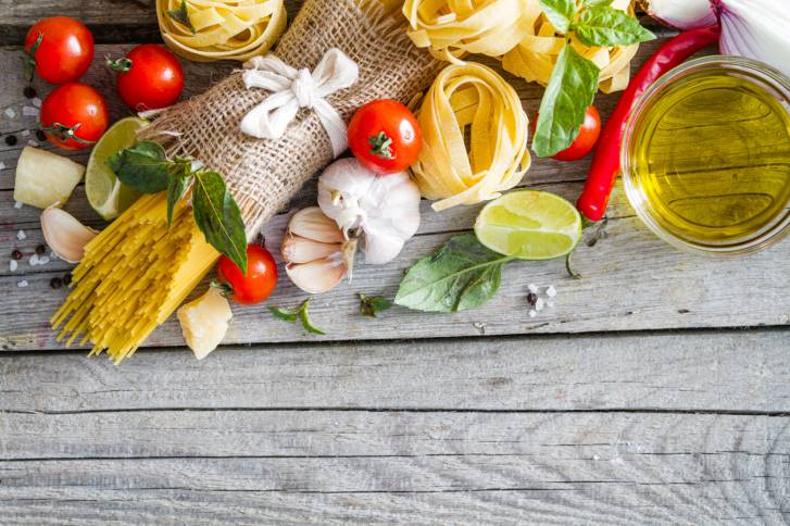 Pasta and ingredients - onion, tomato, basil, garlic, lemon