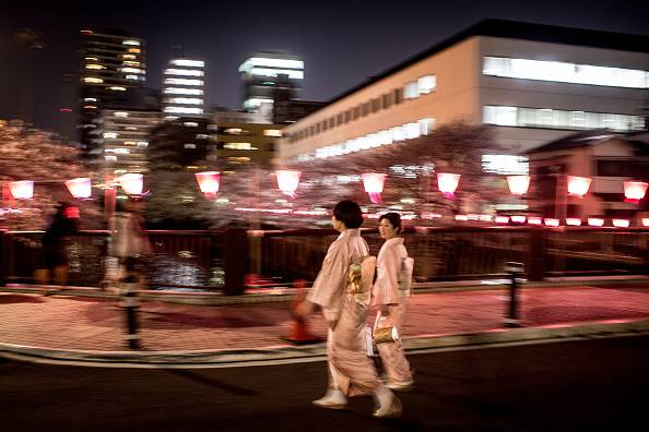"TOKYO, JAPAN - MARCH 31: Two women in traditional dress walk along the river to view cherry blossom trees in full bloom in Meguro, on March 31, 2015 in Tokyo, Japan. During cherry blossom season thousands of people gather across Japan to practice 'Hanami' (Flower-viewing parties) the centuries old tradition of picnicking under a blooming Sakura tree. Hanami is said to have started during the Nara Period and still today people gather wherever cherry blossom trees are blooming and enjoy food and drinks often well into the night. As cherry blossom season coincides with the beginning of the new school year and the beginning of the business year many hanami parties are also used by companies and organizations to welcome new employees and bring staff together. The Cherry blossom season only lasts for an average of two weekends and the ""cherry blossom front"" is forecast each year by the Japan Meteorological Agency as it moves across Japan, it is tracked by many people planning to celebrate Hanami, so as to get a prime position under trees in full bloom, often companies will have younger employees reserve a spot hours or even days before the planned party. (Photo by Chris McGrath/Getty Images)"