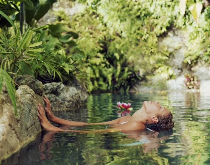 Young woman in spa, leaning head back into water