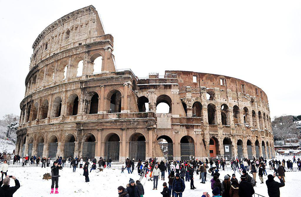 (FILES) This recent file picture taken on February 4, 2012 in Rome shows people standing in front of the Colosseum covered with snow. Italian newspapers reported on February 14, 2012 that heavy snow has caused extensive damage to the medieval walled town of Urbino and further deteriorated the Colosseum in Rome which is badly in need of repair. AFP PHOTO / FILES / ALBERTO PIZZOLI (Photo credit should read ALBERTO PIZZOLI/AFP/Getty Images)