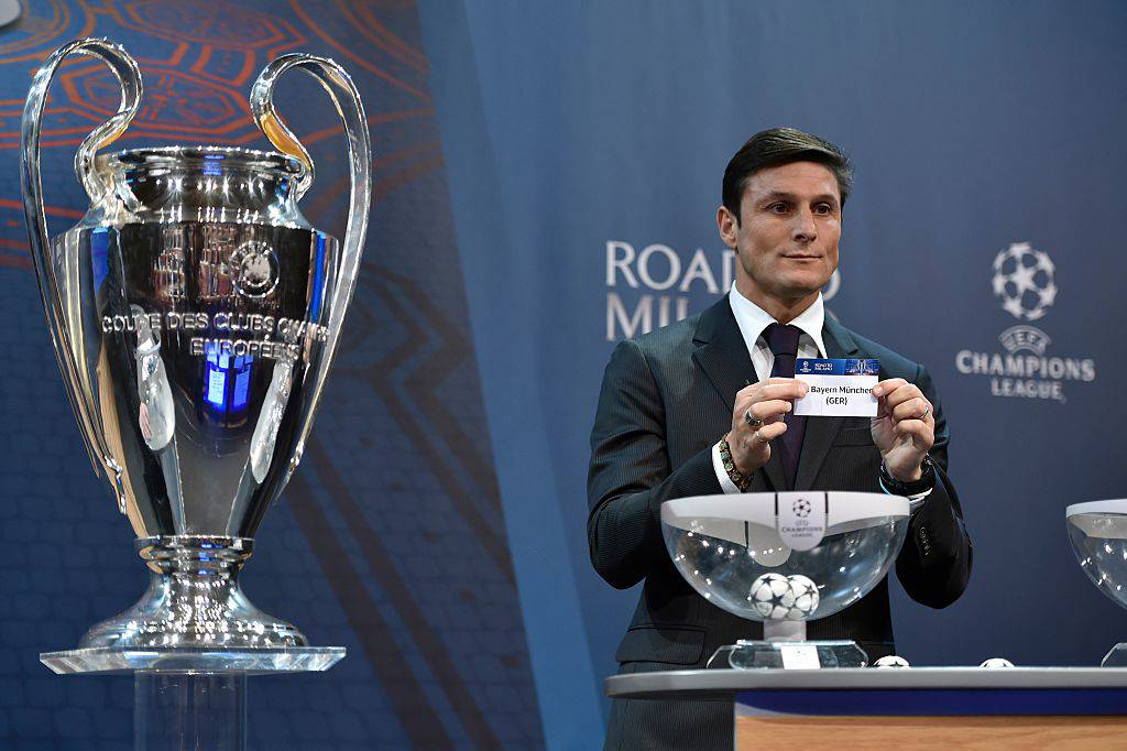UEFA Champions League final ambassador  Javier Zanetti shows the name of FC Bayern Munich football club during the draw for the UEFA Champions league round of sixteen, on December 14, 2015 at the UEFA headquarters in Nyon.  AFP PHOTO / FABRICE COFFRINI / AFP / FABRICE COFFRINI        (Photo credit should read FABRICE COFFRINI/AFP/Getty Images)