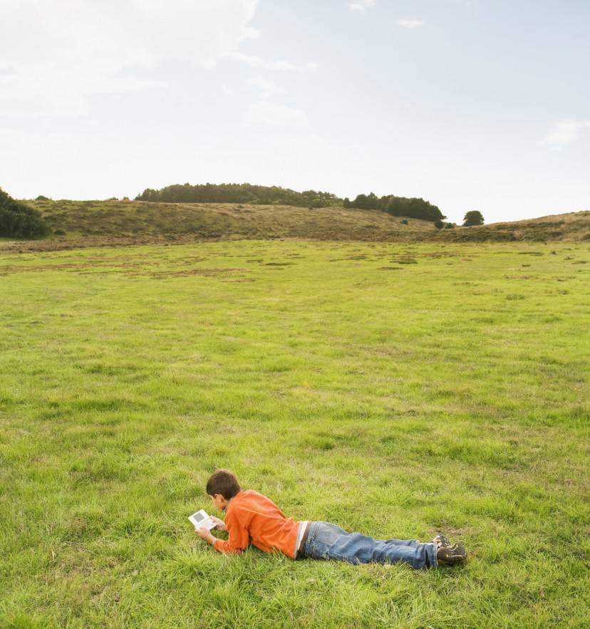 Hispanic boy playing handheld video game in field