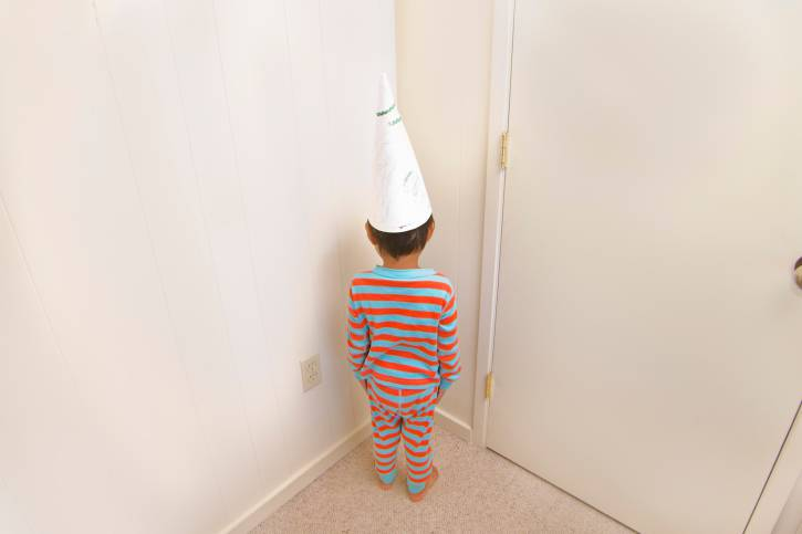 Boy wearing dunce cap in corner