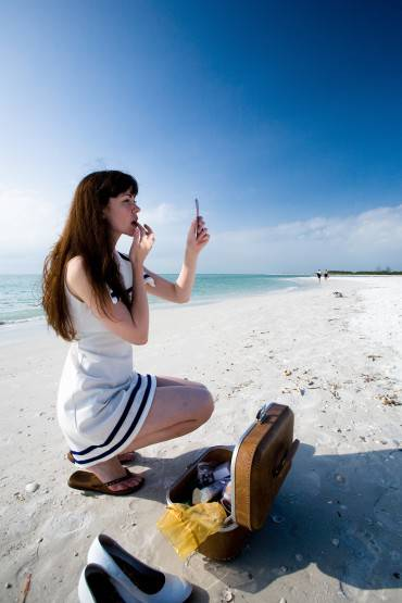 Woman applying lipstick at the beach, Miami, Florida