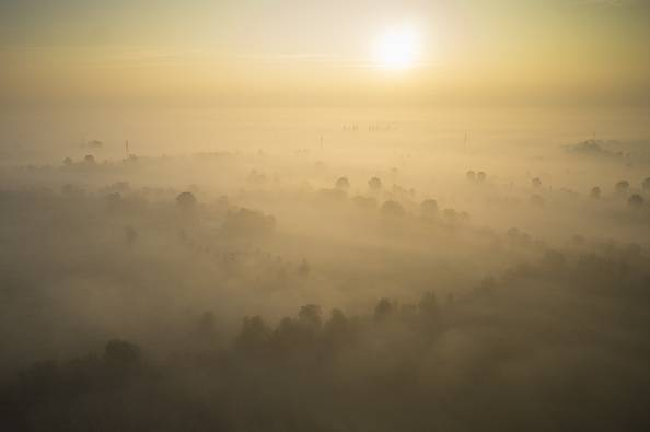 A picture taken on October 24, 2015 shows an aerial view of the sun rising above early morning mist in the countryside near Abbiategrasso, southwest of Milan.  AFP PHOTO / OLIVIER MORIN        (Photo credit should read OLIVIER MORIN/AFP/Getty Images)