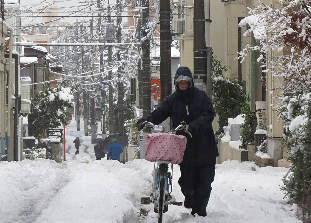 A woman pushes a bicycle along a street covered with snow in Tokyo on January 18, 2016. Tokyo had its first snow of the season amid cold temperatures, with snowfall reaching six centimeters (2.4 inches) in downtown areas. AFP PHOTO / KAZUHIRO NOGI / AFP / KAZUHIRO NOGI (Photo credit should read KAZUHIRO NOGI/AFP/Getty Images)