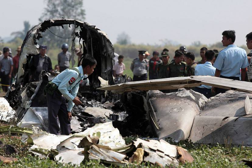 Myanmar army officials inspect the wreckage of a military passenger plane which crashed in a field near the airport in the capital of Naypyidaw on February 10, 2016. Four Myanmar military personnel were killed and one was seriously injured after the small air force propeller plane crashed shortly after take off in the capital Naypyidaw, officials said.    AFP PHOTO / AFP / STR        (Photo credit should read STR/AFP/Getty Images)
