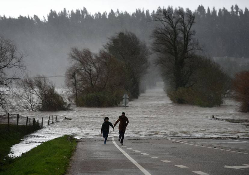A father and his son run to shelter from the rain near a flooded road in Arzila, near Coimbra in central Portugal, on February 14, 2016. / AFP / FRANCISCO LEONG        (Photo credit should read FRANCISCO LEONG/AFP/Getty Images)
