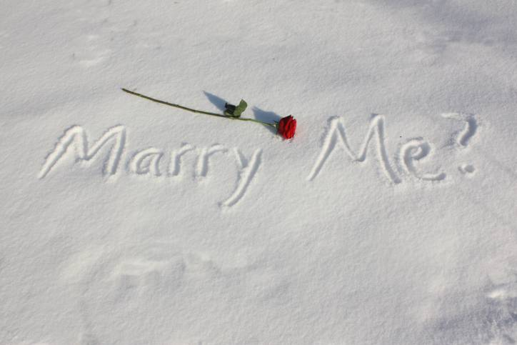 Marry Me? written in snow with a long stem red rose.