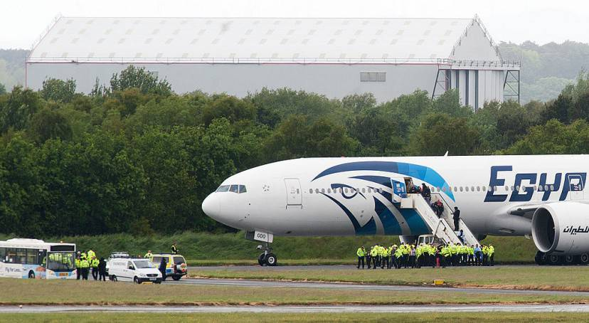 "Police escort passengers off the Egyptair Boeing 777 flight from Cairo that was forced to land at Glasgow Prestwick airport in Scotland on June 15, 2013 en route to JFK airport in New York after an onboard incident. Britain's Royal Air Force (RAF) on June 15 escorted an Egyptair plane bound for New York to a Scottish airport following an onboard incident, the Ministry of Defence said. The Boeing 777 was travelling between Cairo and New York when a passenger alerted plane crew that she had found a note reading ""I'll set this plane on fire"" in the toilet. The message was scrawled in pencil on a napkin and was found by BBC New York producer Nada Tawfik. AFP PHOTO / ANDY BUCHANAN (Photo credit should read Andy Buchanan/AFP/Getty Images)"