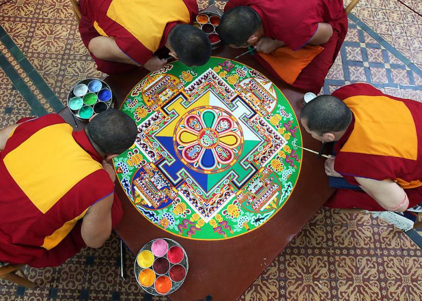 SALISBURY, ENGLAND - OCTOBER 03: Tibetan Monks from the Tashi Lhunpo Monastery , (clockwise from top) Ven Lobzang Thokmed, Kachen Namgyal, Kachen Lobzang Tuskhor and Kachen Choedrak complete a Chenrezig Sand Mandala in Salisbury Cathedrals Chapter House on October 3, 2013 in Salisbury, England. The monks, who started the painstaking process of creating the sand mandela with millions of grains of coloured sand on Monday, will end it tomorrow in a destruction ceremony and procession to the River Avon. The monks who currently live in exile in India are visiting various places in the UK and Europe and will complete two more sand mandelas - which are an artistic tradition of Tibetan Buddhism and are a symbolic picture of the universe representing an imaginary palace - before returning home to their monastery in late November. (Photo by Matt Cardy/Getty Images)