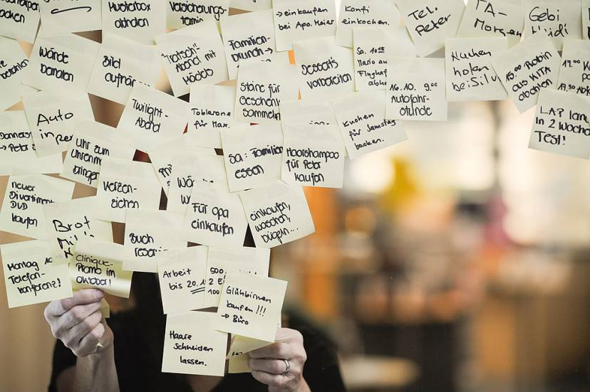 A woman removes some post-it notes, with common tasks to remember written on them,  on a chemist's window in Winterthur on November 7, 2013.         (Photo credit should read SEBASTIEN BOZON/AFP/Getty Images)