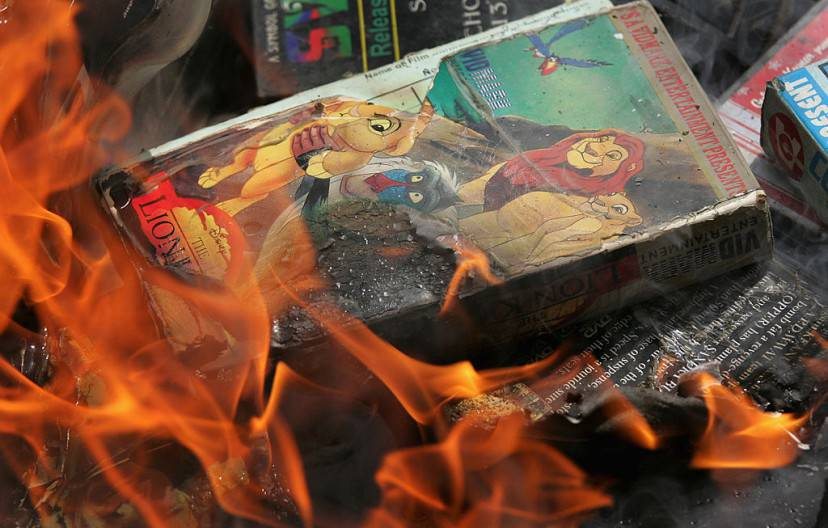 "ISLAMABAD, PAKISTAN - APRIL 06:  A copy of ""The Lion King"" goes up in smoke as students at an Islamic madrassa burn thousands of DVDs, videos and music CDs April 6, 2007 at the Lal Mosque in Islamabad, Pakistan. The event, reminiscent of the early days of the Taliban in Afghanistan, took place within two kilometers of the Pakistani presidential palace, as well as the heavily-fortified U.S. embassy. Thousands of Pakistani soldiers and paramilitary troops were deployed to the capitol in the previous week, and many believe a confrontation between government troops and the students is imminent. Clerics at the mosque, known as the most radical in Islamabad, want Pakistan to adopt a Taliban-style government. They maintain that movies and music are un-Islamic.  (Photo by John Moore/Getty Images)"