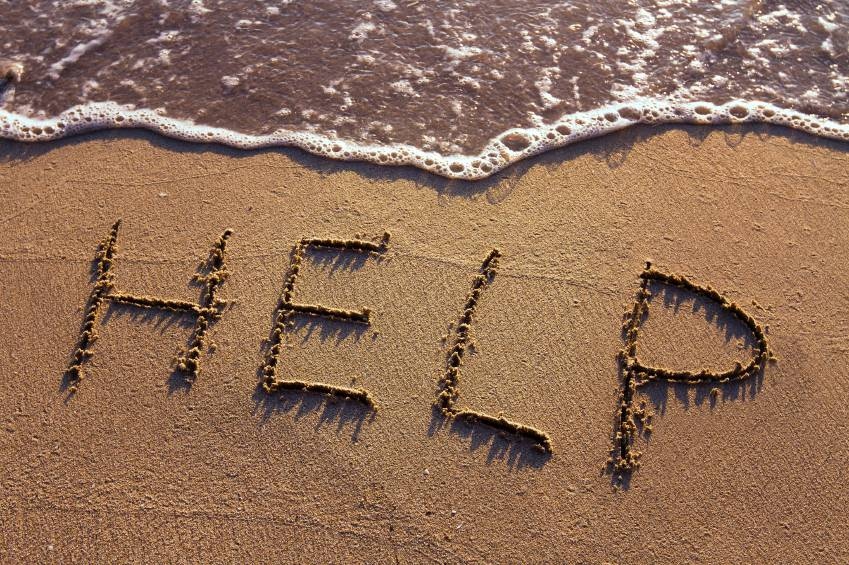 word HELP handwritten on the sand