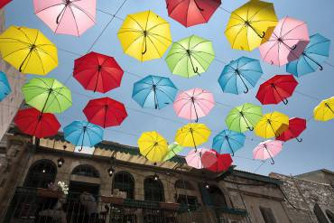 Coloured umbrellas decorate a main pedestrian street in Jerusalem on June 30, 2015, as the city's municipality opens more attractions and cultural activities in an effort to bring tourists and locals to visit the city. AFP PHOTO/MENAHEM KAHANA        (Photo credit should read MENAHEM KAHANA/AFP/Getty Images)