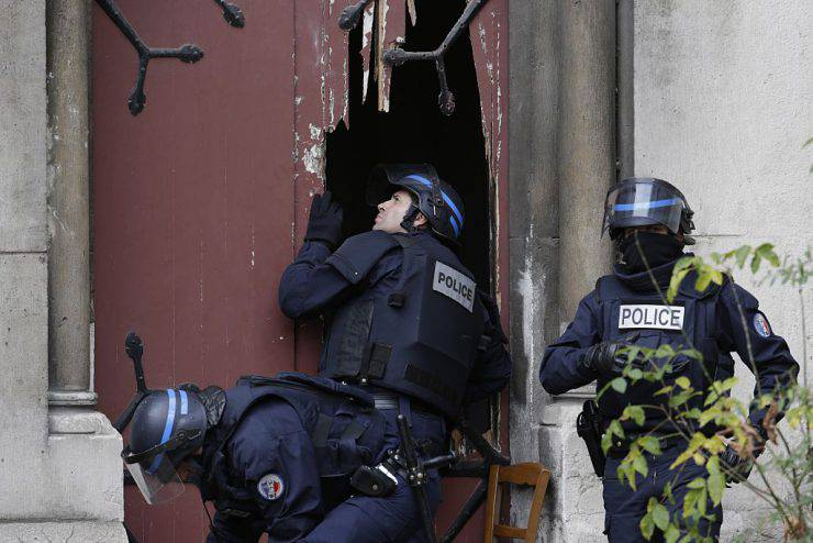 Policemen break a door to enter a church in the northern Paris suburb of Saint-Denis city center, on November 18, 2015, to secure the area after French Police special forces raid an appartment, hunting those behind the attacks that claimed 129 lives in the French capital five days ago. At least one person was killed in an apartment targeted in the operation aimed at the suspected mastermind of the attacks, Belgian Abdelhamid Abaaoud, and police had been wounded in the shootout. AFP PHOTO / KENZO TRIBOUILLARD        (Photo credit should read KENZO TRIBOUILLARD/AFP/Getty Images)