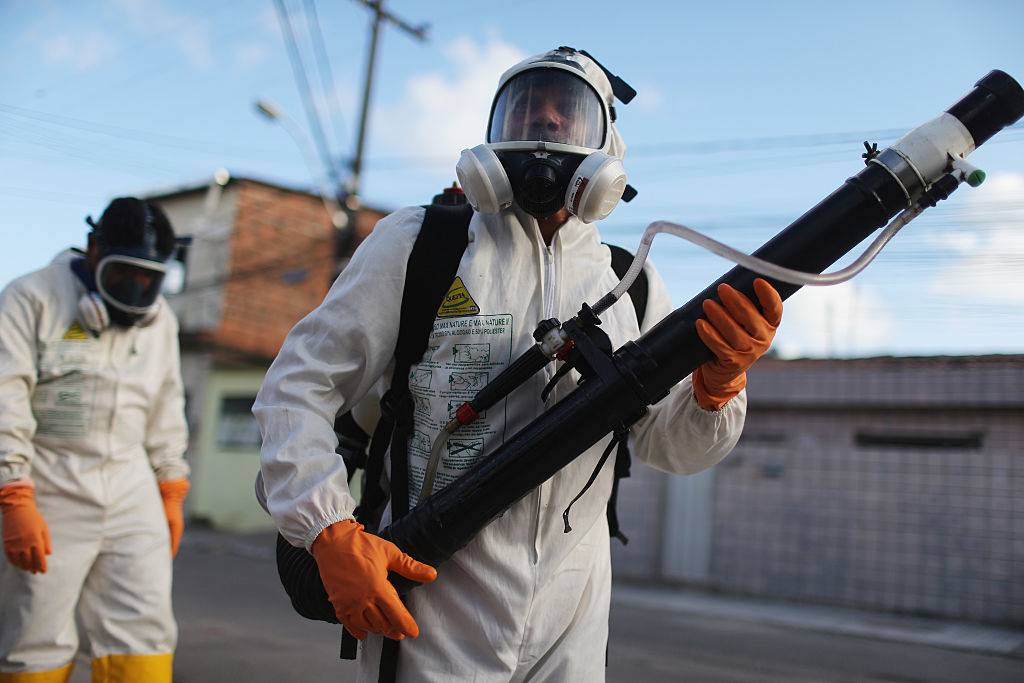 RECIFE, BRAZIL - JANUARY 28:  Health workers fumigate in an attempt to eradicate the mosquito which transmits the Zika virus on January 28, 2016 in Recife, Pernambuco state, Brazil. Two two-man teams were fumigating in the city today. Health officials believe as many as 100,000 people have been exposed to the Zika virus in Recife, although most never develop symptoms. In the last four months, authorities have recorded around 3,500 cases in Brazil in which the mosquito-borne Zika virus may have led to microcephaly in infants. The ailment results in an abnormally small head in newborns and is associated with various disorders including decreased brain development. According to the World Health Organization (WHO), the Zika virus outbreak is likely to spread throughout nearly all the Americas.  (Photo by Mario Tama/Getty Images)