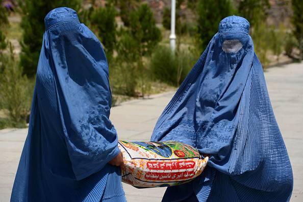 Donne afghane con il burqua mentre portano un sacco con aiuti alimentari a Herat (AREF KARIMI/AFP/Getty Images)
