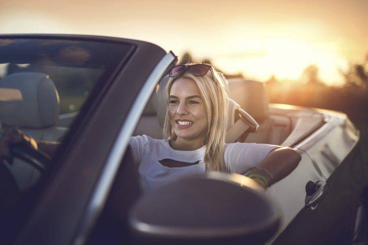 Happy woman driving a convertible car at sunset.
